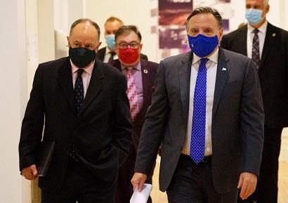 رئيس وزراء كيبيك فرانسوا ليغولت يصل إلى مؤتمر صحفي يحيط به وزير الصحة كريستيان دوبي ، إلى اليسار ، والدكتور هوراسيو أرودا ، مدير الصحة العامة في كيبيك ، في مونتريال ، يوم الاثنين