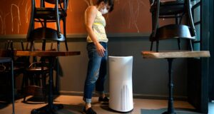 صورة لامراة أمام جهاز تنقية الهواء