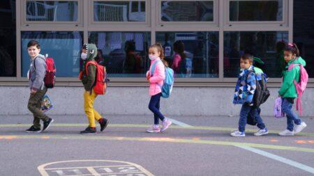صورة لأطقال في طريقهم للمدرسة حيث الأطباء يختلفون حول ما إذا كانت المدارس أساس الموجة الثانية من COVID-19 أم لا