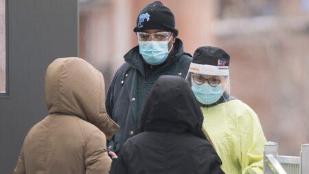 يتحدث أحد العاملين في مجال الرعاية الصحية مع الناس أثناء انتظارهم خارج عيادة اختبار COVID-19 في مونتريال ، يوم الأحد 3 يناير 2021 ، مع استمرار جائحة COVID-19 في كندا وحول العالم. الصحافة الكندية / غراهام هيوز الصحافة الكندية / غراهام هيوز The Canadian Press / Graham Hughes