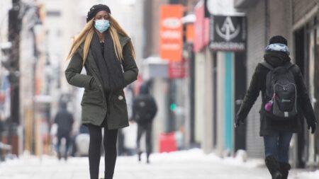 امرأة ترتدي قناعًا للوجه أثناء سيرها على طول أحد شوارع مونتريال ، الأحد 3 يناير 2021 ، مع استمرار جائحة COVID-19 في كندا وحول العالم. الصحافة الكندية / غراهام هيوز