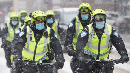 يرتدي ضباط الشرطة أقنعة للوجه أثناء قيامهم بدوريات في الشارع أثناء تساقط الثلوج الخفيف في مونتريال ، الأحد ، 20 ديسمبر 2020 مع استمرار جائحة COVID-19 في كندا وحول العالم. الصحافة الكندية / غراهام هيوز