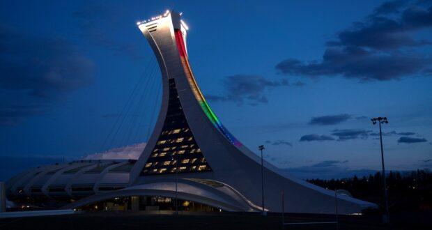 صورة الملعب الأولمبي يضيء بألوان قوس قزح تضامناً مع العاملين في مجال الرعاية الصحية في مونتريال، حيث تطعيمات جماعية لCOVID-19 ستقام خارج ملعب مونتريال الأولمبي