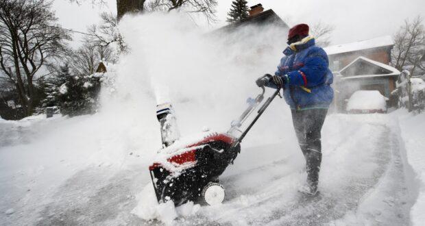 صورة لامرأة تستخدم آلة نفخ الثلج للخروج من الثلج بعد تورنتو ومعظم جنوب أونتاريو تعرضت لعاصفة في تورنتو يوم الثلاثاء ، حيث من المتوقع تساقط ثلوج تصل إلى 25 سم في تورنتو صباح الثلاثاء