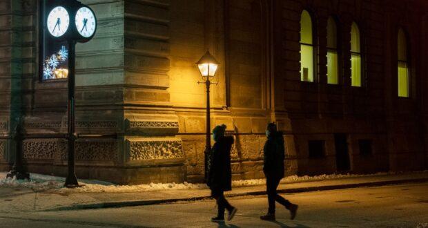 """صورة لناس يرتدون أقنعة للوجه أثناء سيرهم على طول الشارع قبل حظر التجول في مونتريال ، السبت 9 يناير 2021 ، مع استمرار جائحة COVID-19 في كندا وحول العالم. فرضت حكومة كيبيك حظر تجول للمساعدة في وقف انتشار COVID-19 بدءًا من الساعة 8 مساءً حتى الساعة 5 صباحًا.رئيس وزراء كيبيك قد يعلن """"قريبًا"""" عن تخفيف حظر التجول في منطقة مونتريال"""