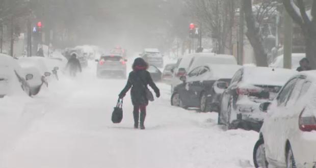 صورة لإمراة تمشي وسط الثلوج في كيبيك في ضوء توقعات بهطول الثلوج في أجزاء من كيبيك في غير موسمها، حيث أن أجزاء من كيبيك قد يصل ارتفاع الثلوج فيها 15 سم جراء تساقط الثلوج في يوم الأربعاء