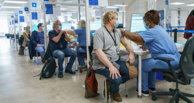 صورة ليتم تطعيم الموظفين في عيادة تطعيم COVID-19 في مقر CAE في مونتريال ، يوم الاثنين ، 26 أبريل ، 2021. بدأ اليوم برنامج إقليمي لتقديم التطعيمات في الشركات الكبيرة في مقر مونتريال لمصنع تكنولوجيا محاكاة الطيران.حجز مواعيد لتلقي التطعيمات أصبح الآن متاحاً لمن في سن الخمسين وما فوق في كيبيك